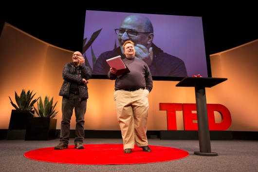 Senior Fellow Taghi Amirani receives the first-ever TED Fellow Hero award from Tom Rielly on the Fellows Talk stage.
