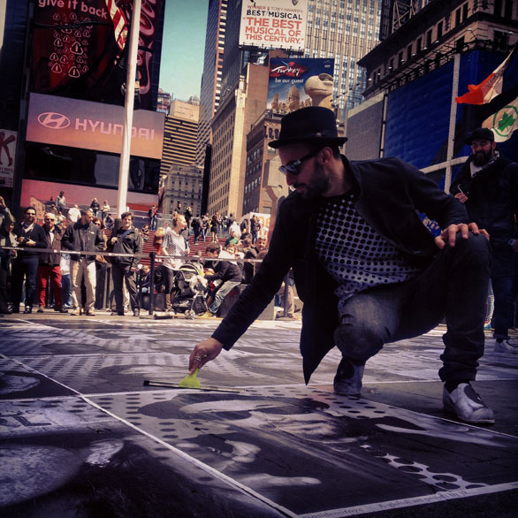 The artist himself examines portraits pasted in Times Square. Photo: Anna Verghese
