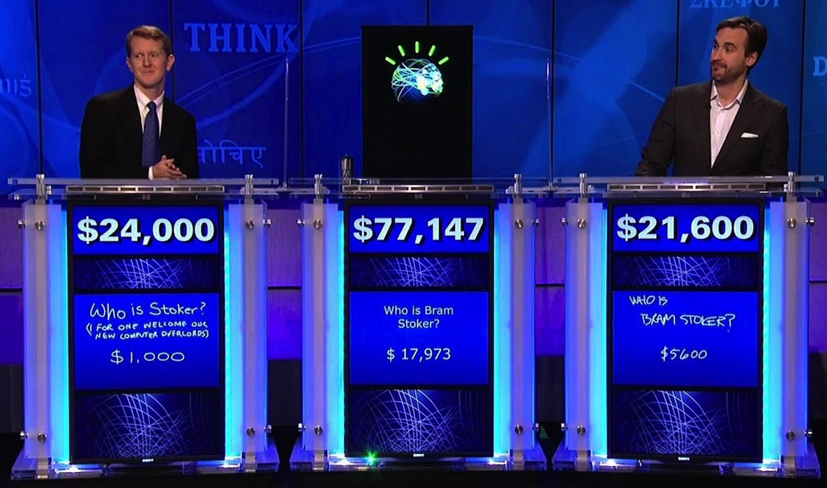 Ken Jennings (left) faces off against supercomputer Watson (center) and his fellow Jeopardy champion, Brad Rutter (right).