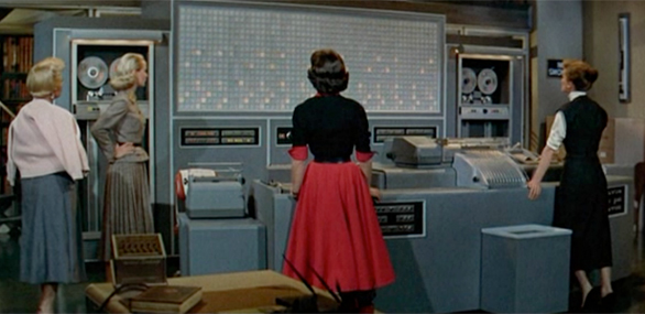 A scene from the 1957 movie Desk Set, starring Spencer Tracy and Katharine Hepburn, with a mainframe computer in the leading role.