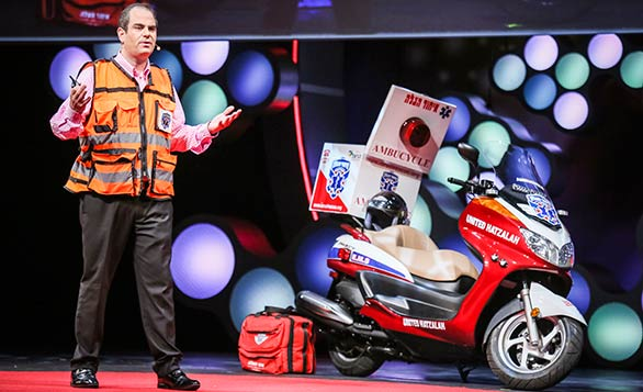 """Eli Beer stands beside one of the """"ambucycles"""" that he and other United Hatzalah EMTs ride. Photo: Courtesy of TEDMED"""
