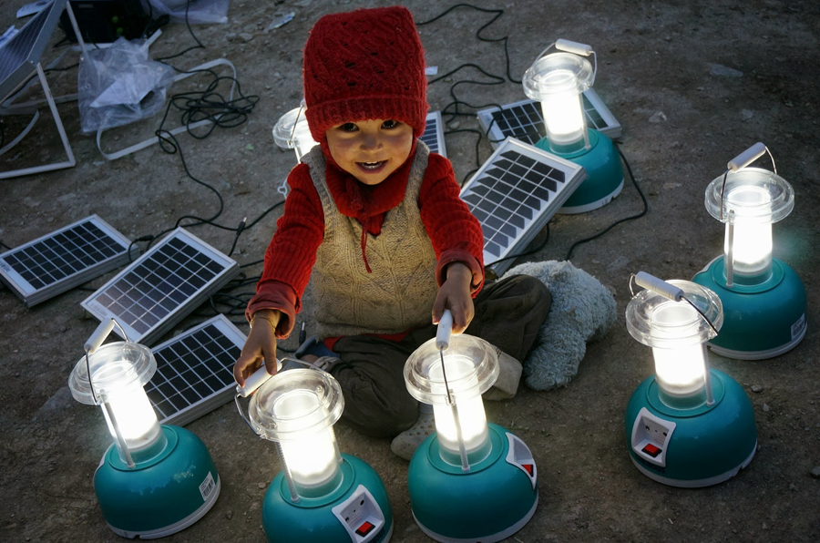 A Sumda Chenmo child experiences solar lanterns for the first time. Solar improves safety, productivity and indoor air quality. Photo: Stephanie Wolcott