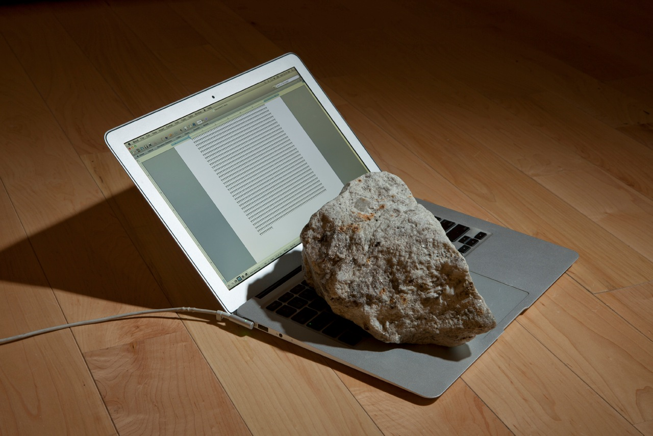 """Present Perfect (2013). A rock sits on the keyboard of an open laptop, typing the letter Y into in infinity in Microsoft Word. Image courtesy of Alicia Eggert."""""""