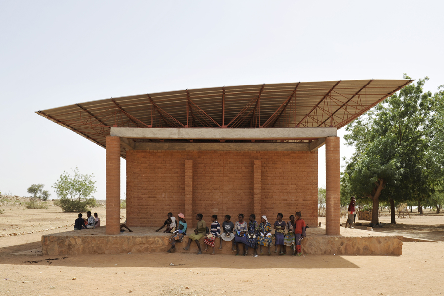 A group of women and girls enjoy the shade outside the primary school. After completion of the building, local authorities opted to pay for the teaching staff. Photo: Erik-Jan Ouwerkerk
