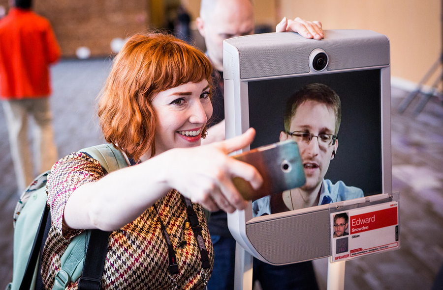 A TED attendee snaps a photo with Edward Snowden, appearing on the screen of a telepresence robot. Photo: Bret Hartman