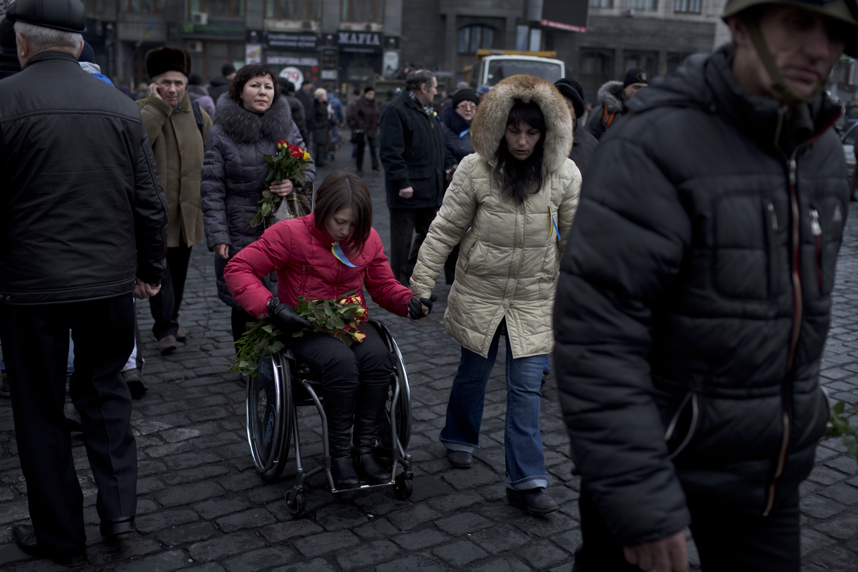 Women distribute flowers to anti-government protesters guarding the barricades in Independence Square in Kiev, Ukraine on Feb. 23, 2014. (Ed Ou/Reportage by Getty Images)
