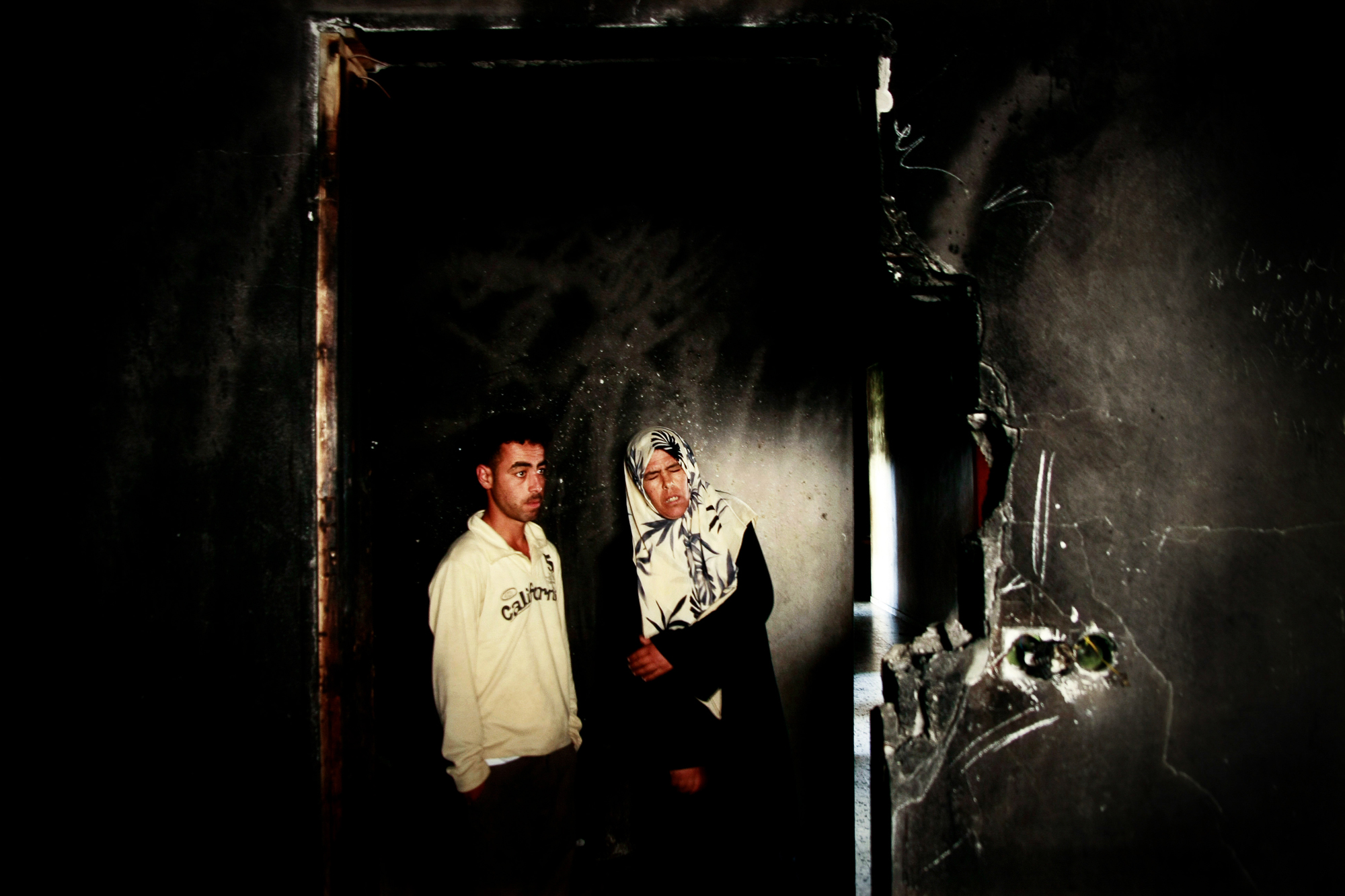 Sabha Abu Halima and her son Ahmed Abu Halima in their house, which was destroyed by fire from phosphoric bombs dropped by Israel during Gaza War. Photo: Eman Mohammed
