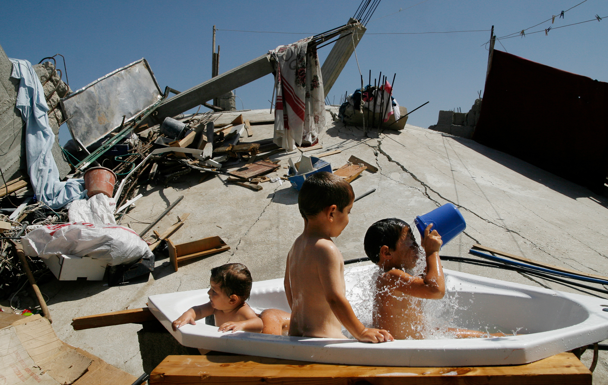 Children having a bubble bath in a Jacuzzi tub sitting atop the rubble of their house, destroyed by Israeli forces. Photo: Eman Mohammed