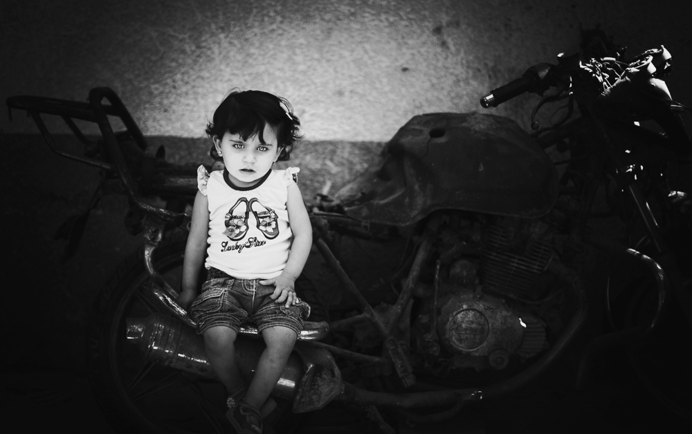 Islam Qreqe ,14 months old, sitting on a burned motorcycle. Her father, uncle and 2-year-old brother were riding it when they were targeted, bombed and killed by a rocket fired from an Israeli aircraft drone. Four months later, Islam was born and named after her brother. (Stay tuned for a gallery of Eman's iWar images next week.) Photo: Eman Mohammed