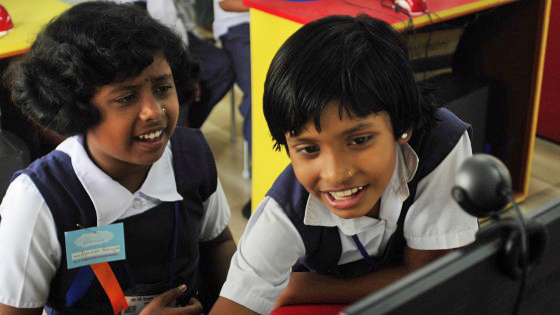 Students at the School in the Cloud in India excitedly figure out how to use a computer. Photo: Courtesy of Jerry Rockwell