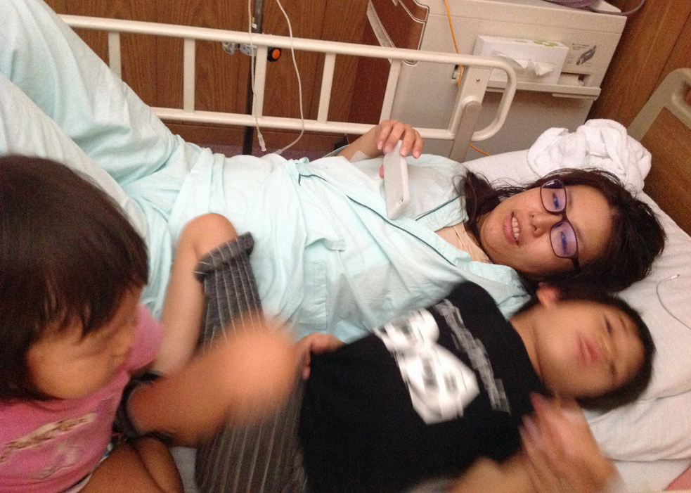 Ai Tokimatsu watches a TED Talk on her phone in the hospital, with her two children. Photo: Courtesy Ai Tokimatsu