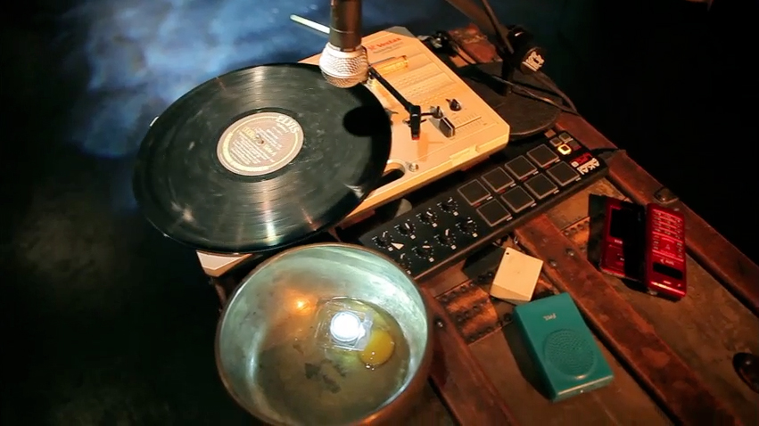 Record player, bowl, egg. A still from the workshop performance of Sunken Cathedral.  Directed by Glynis Rigsby.  Photo: Ash Hsie