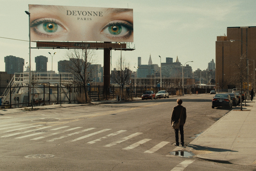 "Molecular biologist Ian (aka Michael Pitt) stares at a billboard of a pair of green eyes in Mike Cahill's film ""I Origins."" Photo: Fox Searchlight"