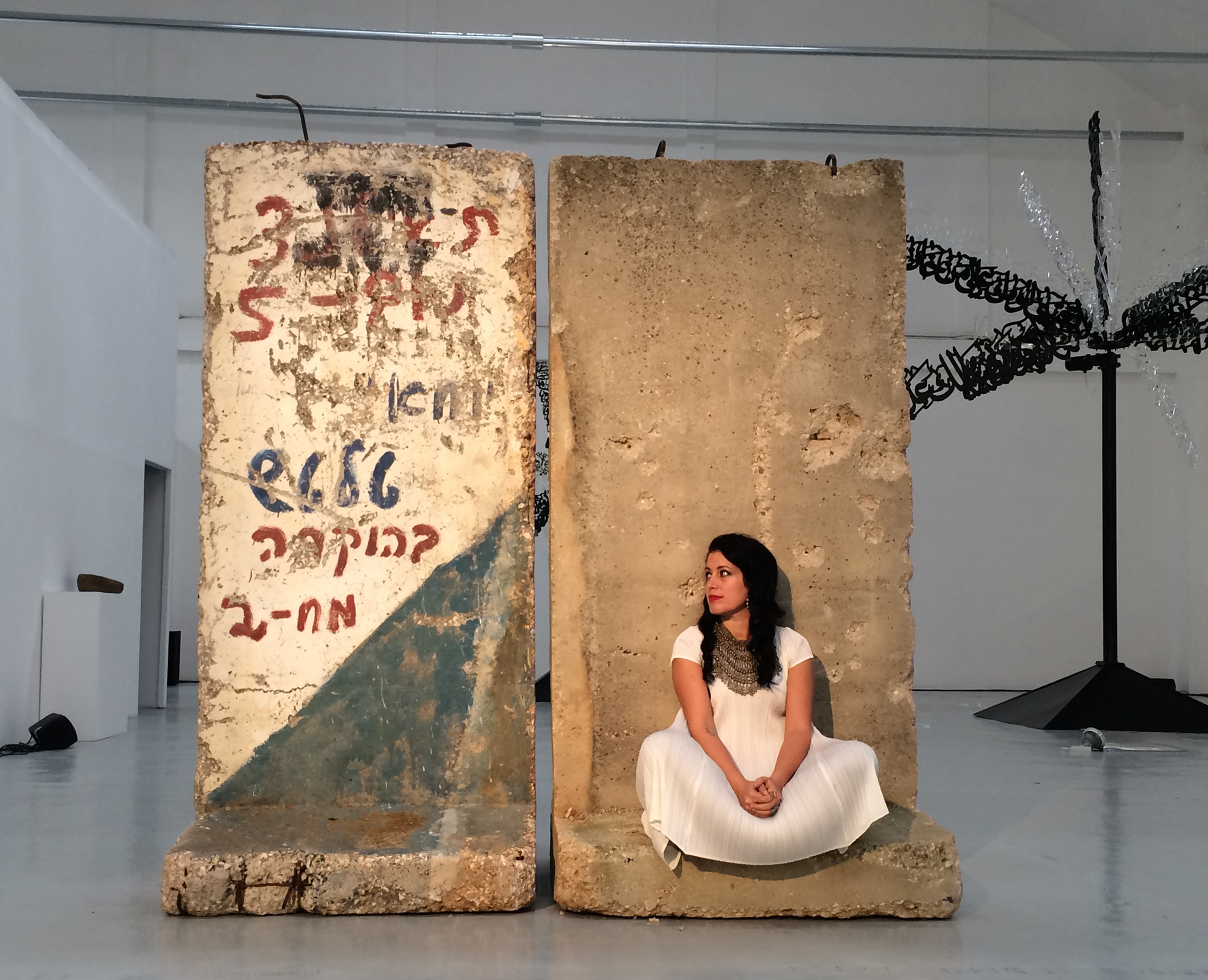 Zena el Khalil poses in the midst of her new exhibit, which makes the rubble of her mother and father's homes in Lebanon into beautiful art. Photo: Eva Zayat