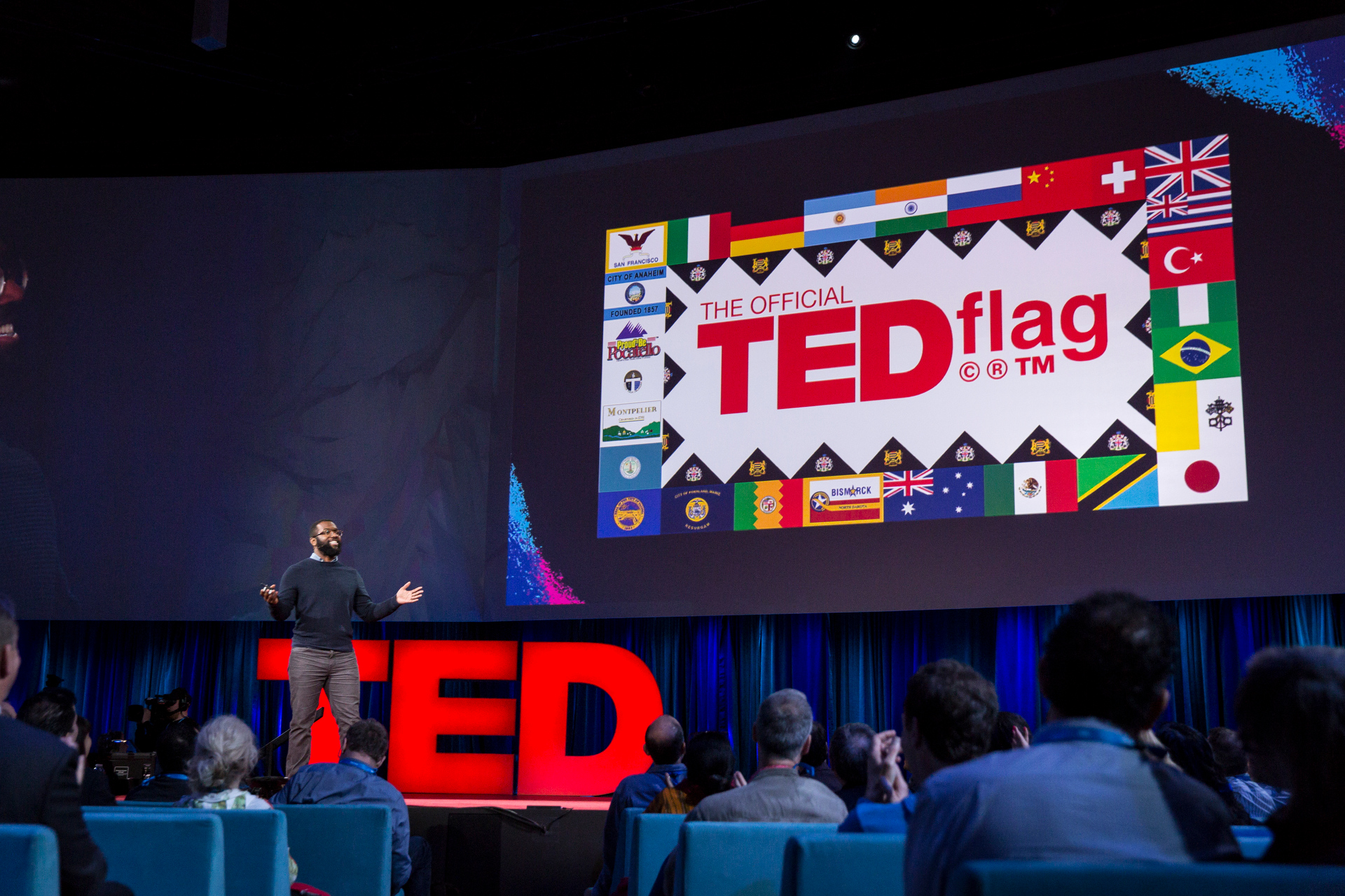 """In his wrap-up of TED2015, Baratunde Thurston unveiled the """"TED Flag."""" It breaks every single rule for flag design laid out in Roman Mars' TED Talk earlier in the week. Photo: Bret Hartman/TED"""