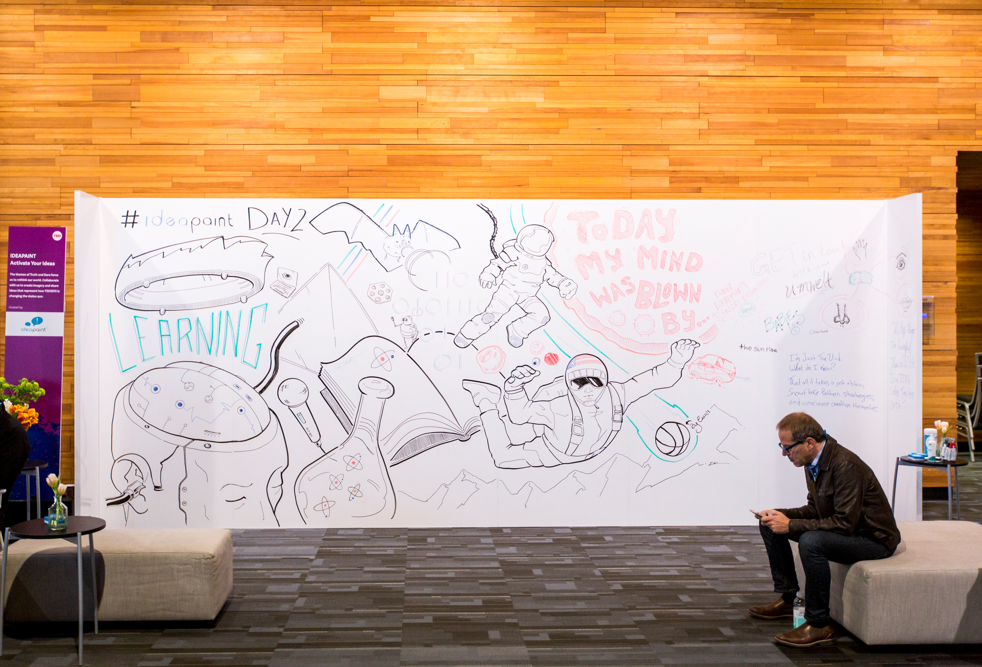 Over at the IdeaPaint wall, attendees are encouraged to draw on the wall and add to Derek Cascio's designs. Photo: Ryan Lash/TED