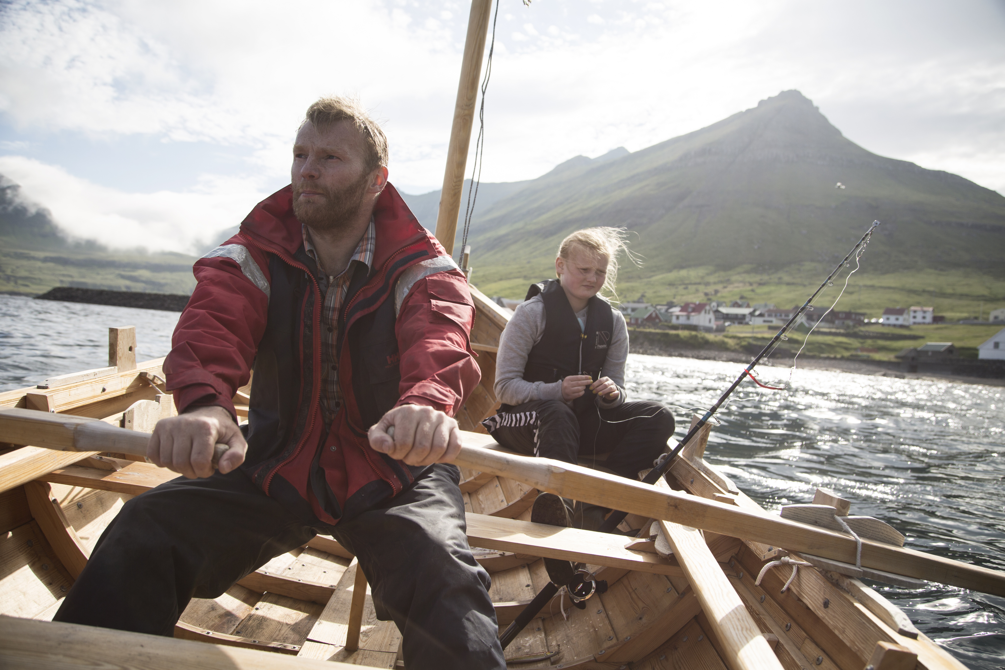 Martin Fløghamri fishes with his daughter in their home town of Oyndarfjørdur, Faroe Islands on July 23, 2014. Photo: Ed Ou