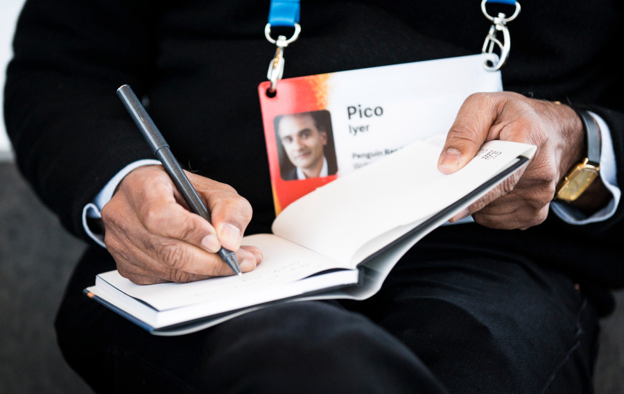 Pico Iyer signs a copy of his TED Book, The Art of Stillness. This week he reviewed David Brooks' latest. Photo: Ryan Lash/TED