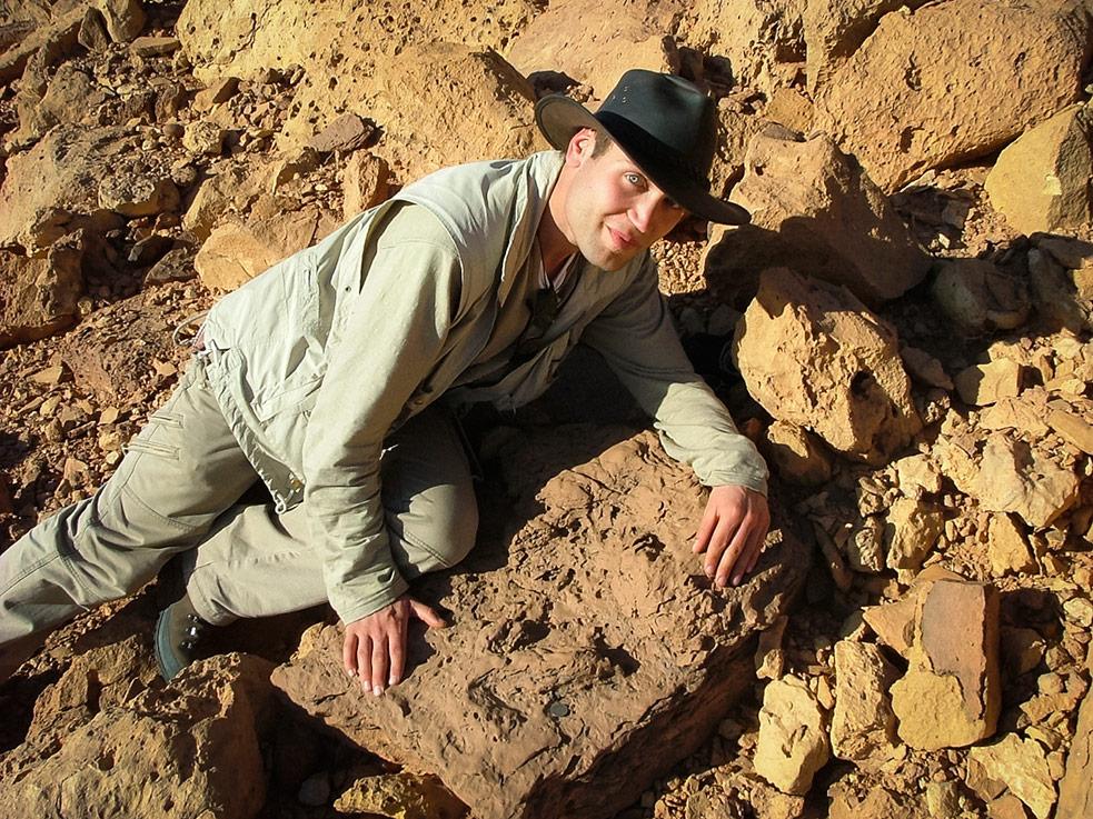 Paleontologist Nizar Ibrahim with the footprint of a predatory dinosaur, in  Gara Sbaa, southeastern Morocco, near the Algerian border. Photo: Robert Loveridge
