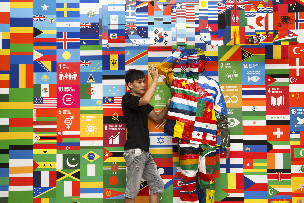 """The future starts now: Chinese artist Liu Bolin's latest work, 'The Future,' has him blending into a collage of flags to raise awareness for the UN's Global Goals. """"I hope that through this work, more and more people will become aware of how serious the issues we face are,"""" he says. Photo: Getty Images, courtesy of the UN"""