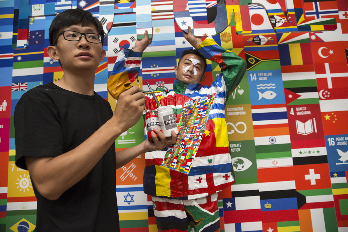 In an assistant's hand, a glimpse at the process used to make Liu Bolin blend perfectly into a background. The key? A scale image to show what's behind him. Photo: Getty Images, courtesy of the UN