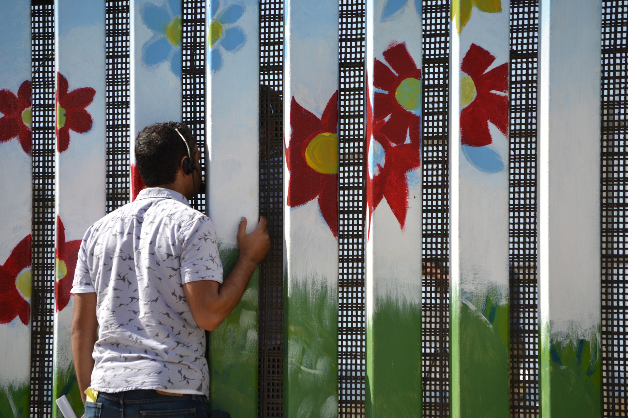 The coordination of the two sides happened through the most low-tech of methods: shouting through the fence. On the US side, the fence looks austere — but on the Mexican side, it's painted with murals. Photo: Arturo Loaiza/TEDxMonumento258
