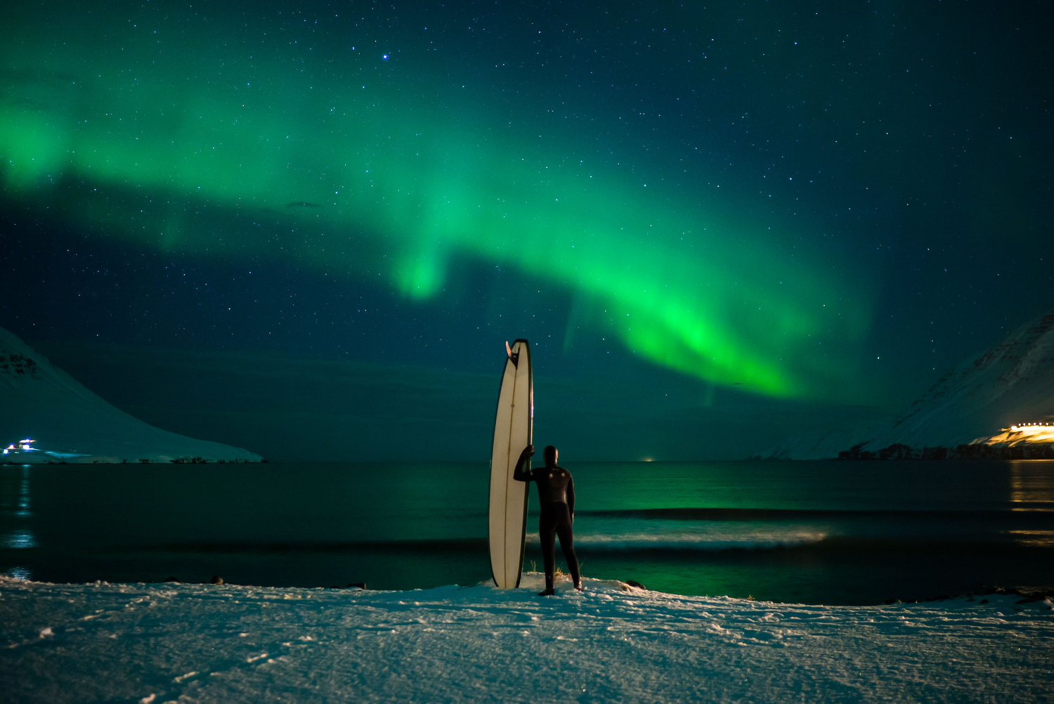 man standing on snowy coast with surf board looking out over the water with northern lights above