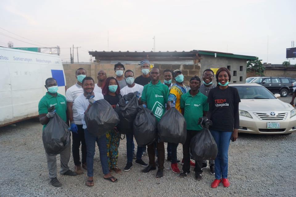 A group of volunteers stand together holding full trash bags and smiling.