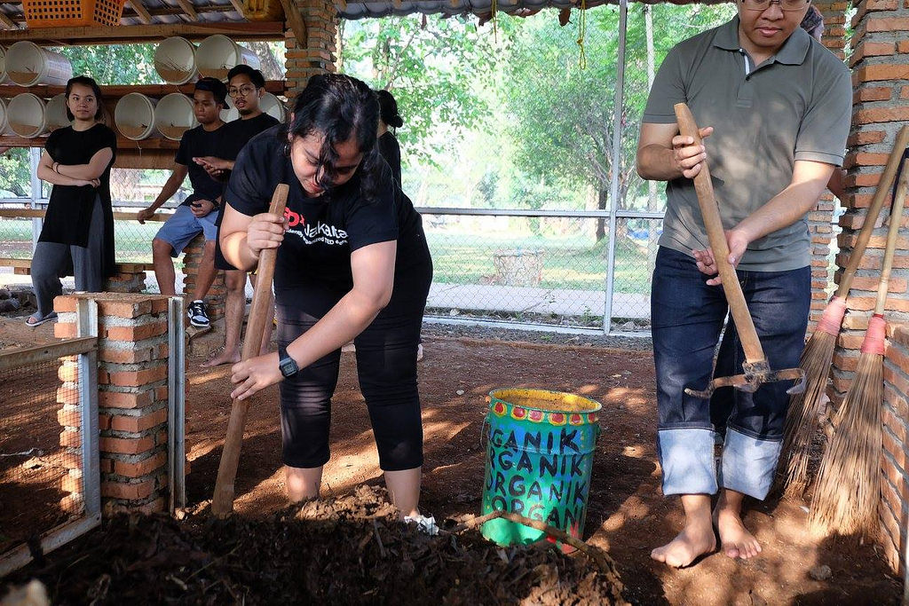 A woman leans down to till earth and compost.
