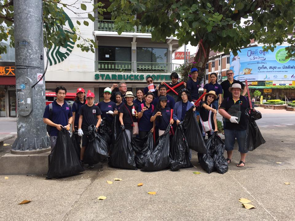 A group of people stand together holding full trash bags.