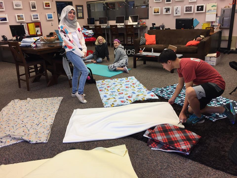 A young woman stands amid laid out blankets in a room, as a man lays another out.
