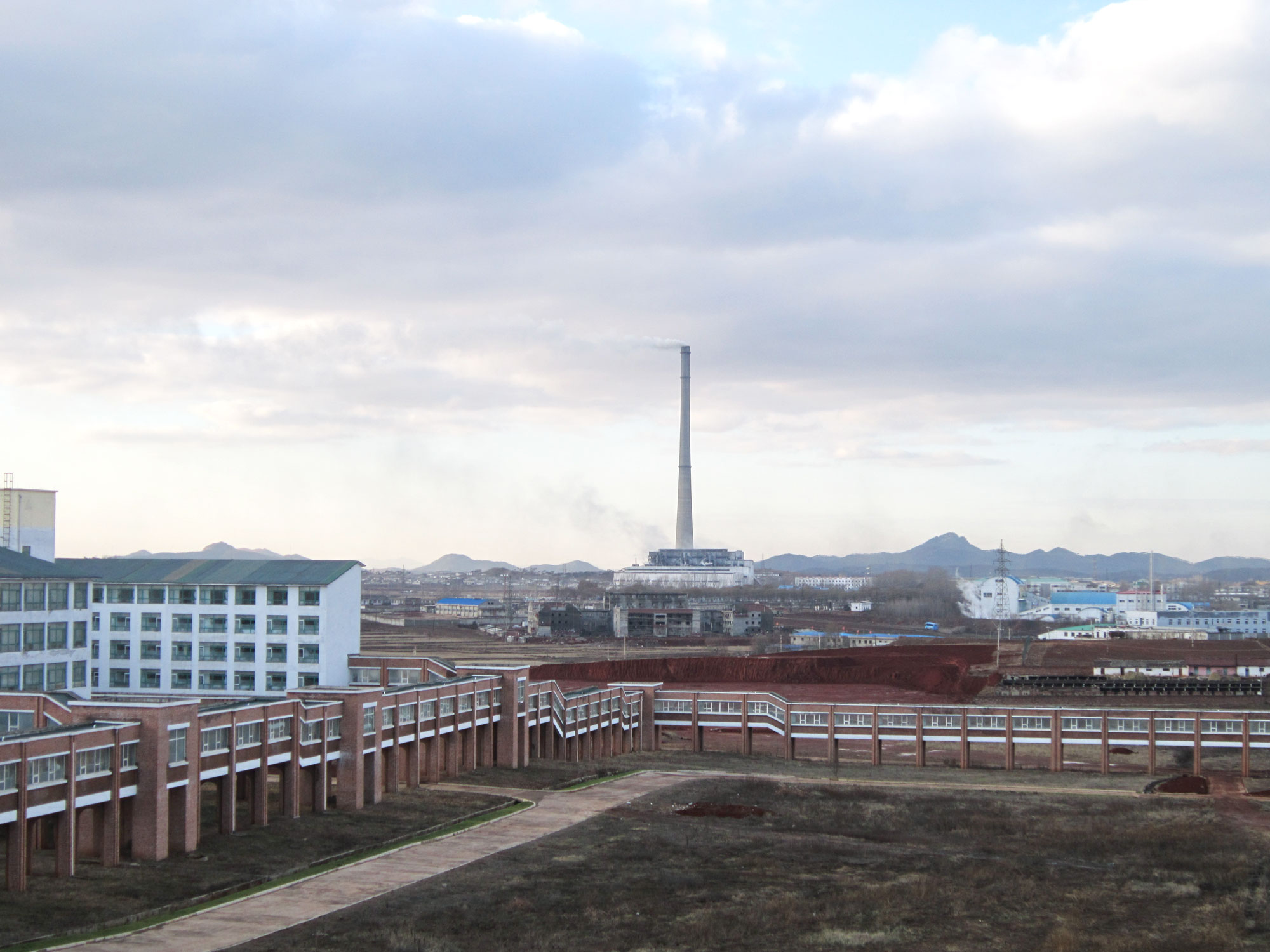 The PUST campus: the enclosed walkway connects all the buildings. The classroom building is on the left; a Pyongyang smokestack can be seen in the distance.