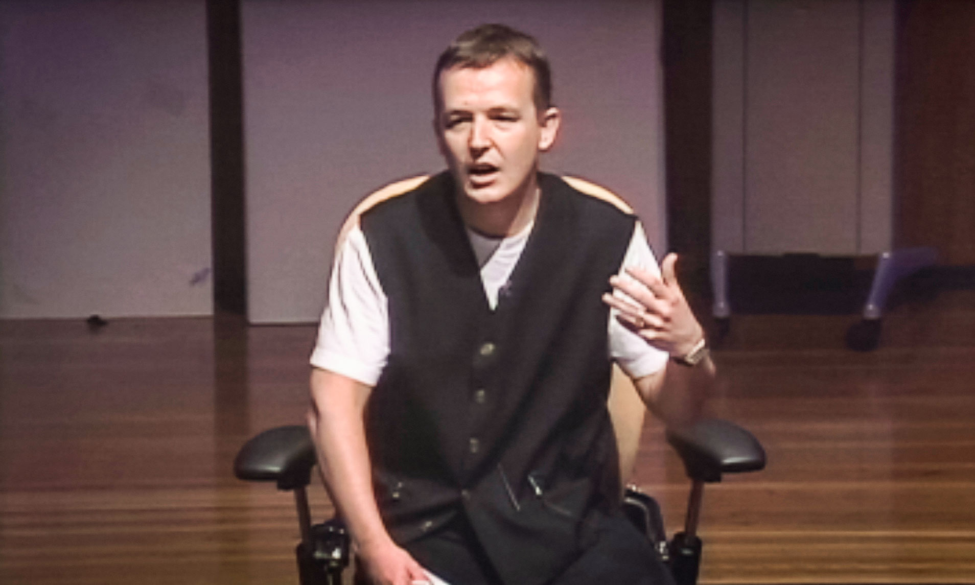 Too nervous to stand, Chris Anderson addresses the 2002 TED audience from a chair, ultimately inspiring them to follow his lead in forging TED's next chapter. Video still courtesy of TED.